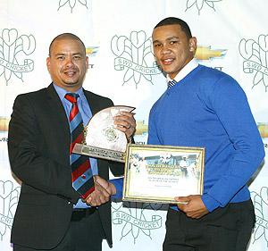 Marcello Piedt receives the trophy for Player of the Season from SWD Cricket President, Rudy Claassen.