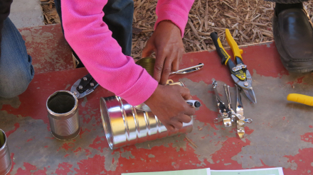 One of the peer educators ladies busy building a stove from waste material