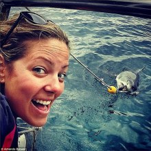Shark selfie: Brewer, pictured here with a much smaller shark, traveled to Africa to volunteer as a scientific data collector for White Shark Africa