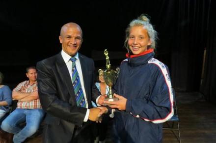 Cllr Daniel Maritz, Deputy Mayor of George, hands a trophy to Mariaan Liebenberg from Kathu High School for excellence in u/17 Netball.