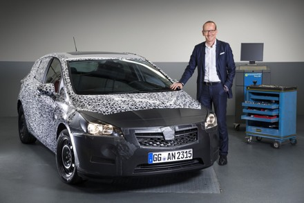 Dr Karl Thomas-Neumann with a camouflaged version of the next generation Opel Astra.  Picture: QuickPic