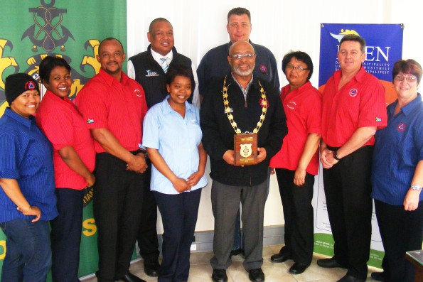 Eden Acting Executive Mayor, Cllr Lionel Esau, hands the trophy to the team consisting of (fltr back): Suenell Atkinson, Cathleen Herdien & Llewellyn Levendal, Wouter Jacobs (4th right), Eileen Trimm (5th, right), Gerhard Otto (DMISA WC Branch Chairperson), Tippie Bouwer (right) and Veronica Maxim (front, left), who assisted with registration, security and other logistics. With them is Executive Manager Clive Africa (Back, 4th left). Marillia Veldkornet (Media Coordination and Photography) and Mercia Xolani (Registration) were not present when the photograph was taken.