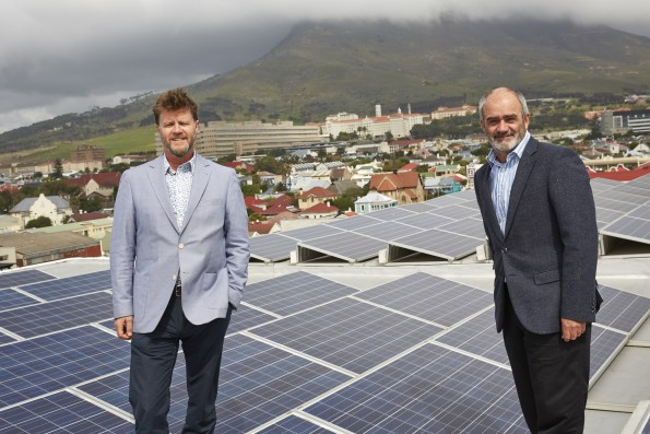 Caption: Anthony Stroebel, group marketing director of Pam Golding Properties and a newly-appointed director of the Green Building Council of South Africa, seen with Brian Wilkinson, CEO of the GBCSA among the photovoltaic solar panels on the roof of Black River Park in Woodstock, Cape Town, home to the headquarters of the GBCSA. Black River Park, which comprises eight buildings, was named the first Green Star SA rated office precinct in the country and the first to receive a 6 Star, Green Star Existing Building Performance rating, and has one of the world's largest roof mounted solar PV systems on the continent