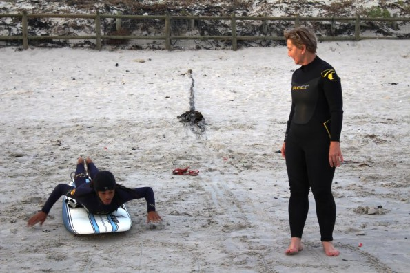 9Miles facilitator, Nathaniel Stemmet, teaching Minister Marais the basics of surfing