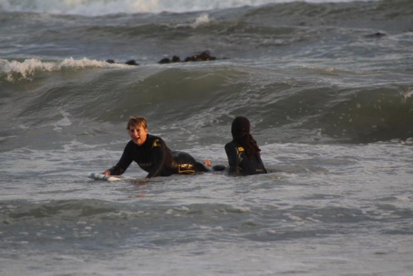 Minister Marais surfing the waves under the guidance of 9Miles project facilitator Nathaniel Stemmet