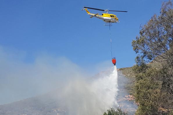 Een van die Huey-helikopters besig om die vuur met water te bestook