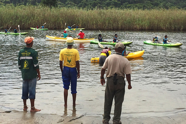 Meneer Moses, people & Conservation Officer, SANParks, assists learners with the skill of canoeing and water safety