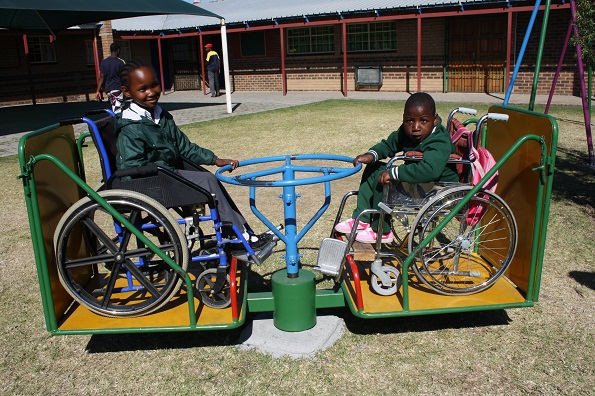 Basizeni School learners discover the joys of playground equipment for the first time. On the roundabout are Retshepile Mbonani and Zinhle Ngcobo. Casual Day funds at Basizeni School go towards upgrading the school playground. These swings were custom-designed for the children in wheelchairs. On the swingsare Winile Sibiya and Zinhle Ngcobo