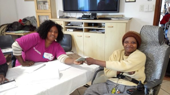 Official Masabatha Selekane (left) assists resident Winky Peter at the special voting station set up at Cheshire Homes on Tuesday. Photo: Full Stop Communications