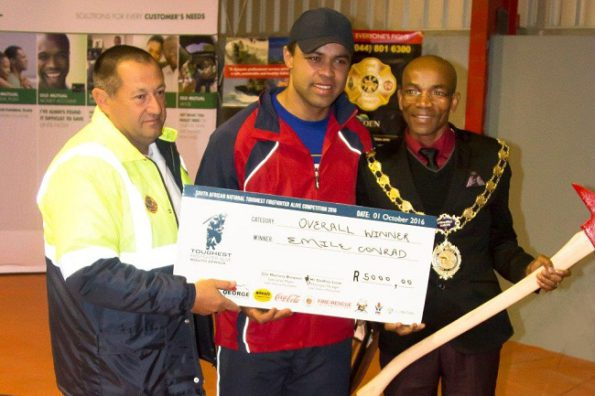 Mr Emile Conrad – overall winner of the 2016 SA Toughest Firefighter Alive Competition receiving his cheque of R5000 and a fireman's axe from Eden DM Executive Mayor, Cllr Memory Booysen (right) and Mr Deon Stoffels, Deputy Fire Chief (left) of Eden DM